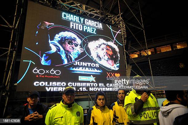 Police officers stands next to a sign for the concert of Argentine musician Charly Garcia and Fito Paez after the announcement that Garcia had had...
