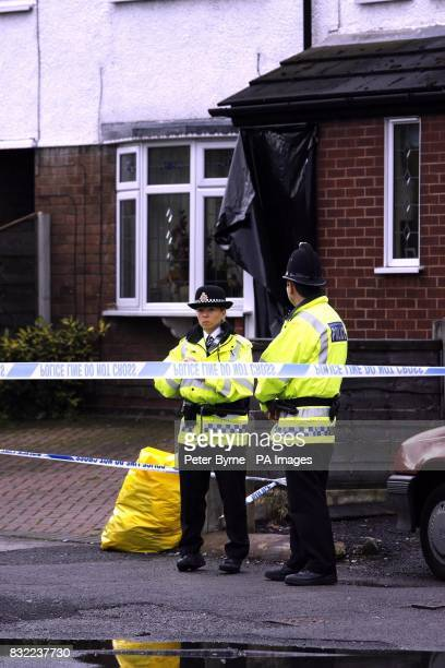 Police officers stands outside a house in Turves Road Cheadle Hulme in Manchester