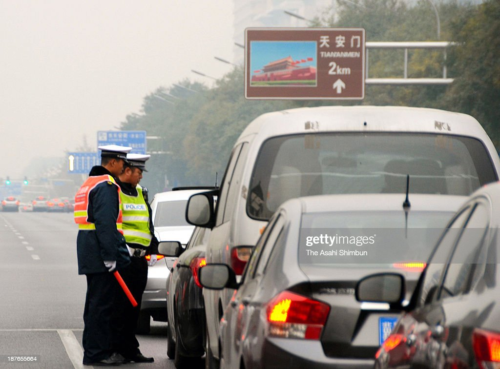 Police officers stop motorists bound for Beijing's Tiananmen Square ahead of the third plenary session of the 18th Central Committee of the Chinese Communist Party on November 9, 2013 in Beijing, China.