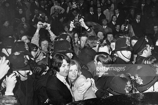 Police officers surround Paul McCartney and new wife Linda McCartney as they make their way through fans following their marriage in London