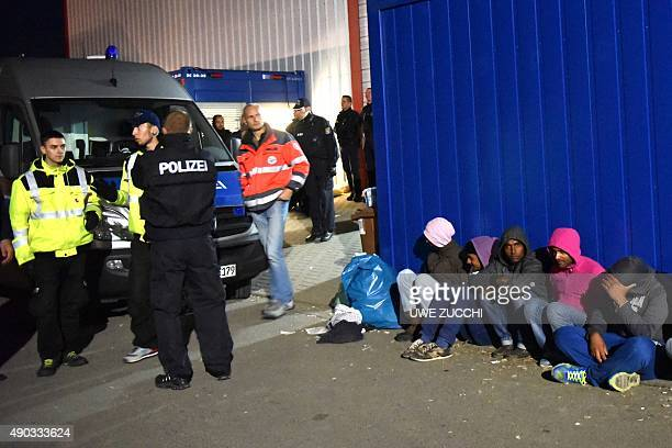 Police officers survey as refugees sit outside a migrants shelter in Calden near Kassel on September 27 2015 where clashes erupted between hundreds...