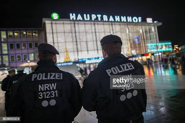 Police officers survey the area in front of the main train station and the Cathedral in Cologne western Germany on January 6 where dozens of...