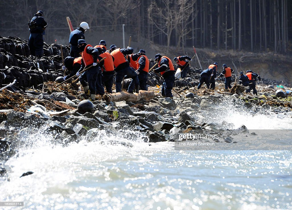 Police officers sweep through a coast to search missings on March 11, 2013 in Rikuzentakata, Iwate, Japan. On March 11, Japan marks second anniversary of the Magnitude 9.0 earthquake and subsequent tsunami, that claimed more than 18,000 lives.