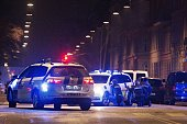 Police officers take cover behind their patrol cars on the streets of central Copenhagen on February 15 2015 after one person was shot in the head...