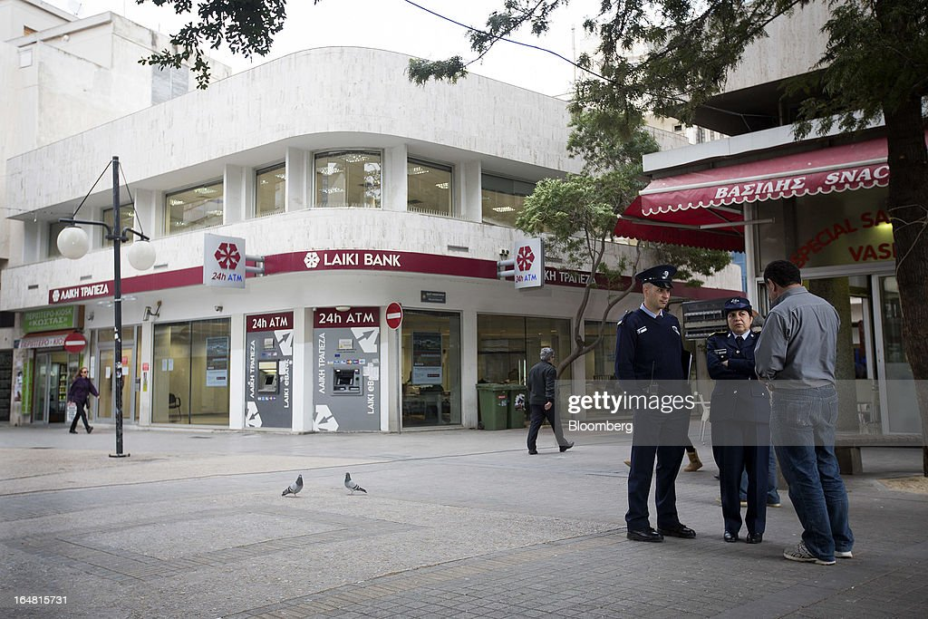 Police officers talk to a man outside a branch of Cyprus Popular Bank Pcl, also known as Laiki Bank, as banks open for the first time in two weeks in Nicosia, Cyprus, on Thursday, March 28, 2013. The Central Bank of Cyprus's capital controls will include a 300-euro ($383) daily limit on withdrawals and restrictions on transfers to accounts outside the country. Photographer: Simon Dawson/Bloomberg via Getty Images