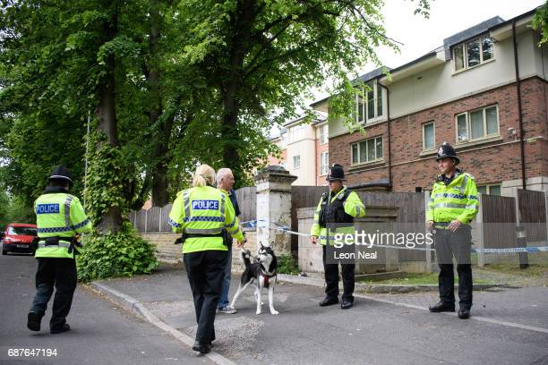 Police officers talk to a member of the public as they guard the location of a building where it is believed a raid took place in connection with...
