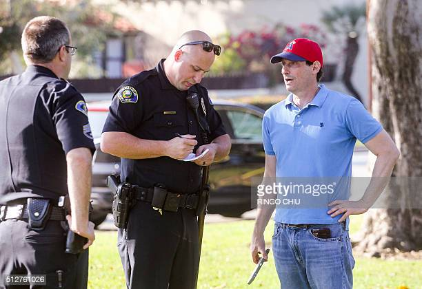 Police officers talk to a witness after three counterprotesters were stabbed while clashing with Ku Klux Klan members staging a rally in Anaheim...