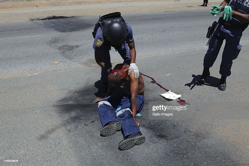 Police officers tend to a wounded protestor on January 22, 2013, in Sasolburg, South Africa. The announcement of government's intention to merge municipalities in the Free State sparked outrage in Zamdela township residents.