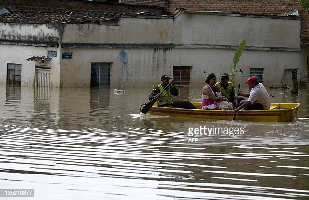 Police officers transporting a woman and her son in a plastic boat on a flooded street following the overflowing of the Cauca River on December 7 in...