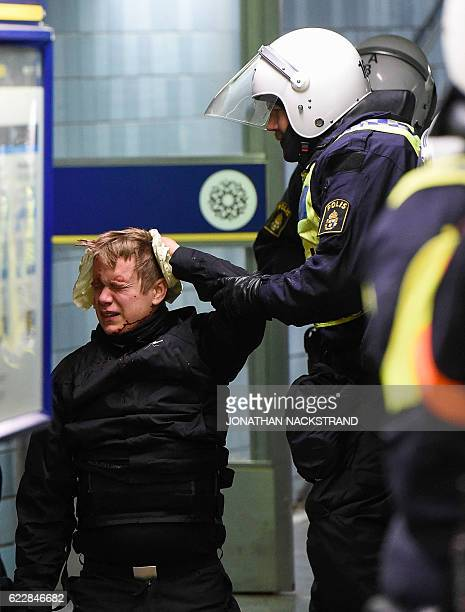 Police officers treat an injured protester from the neonazi Nordic Resistance Movement in central Stockholm on November 12 2016 after a protest...
