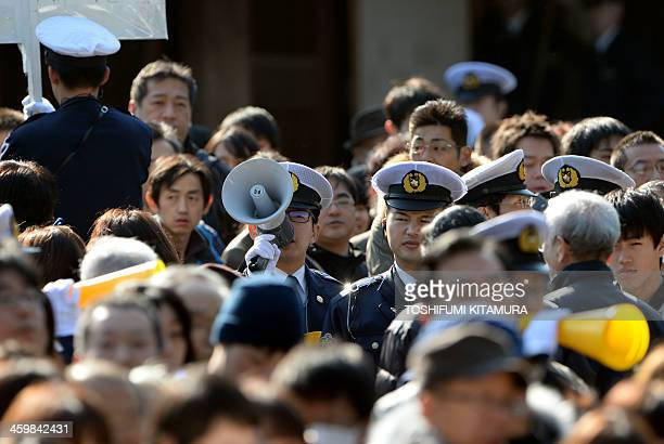 Police officers try to control the crowds as people pack the grounds at Meiji shrine in Tokyo on January 1 2014 About three million people were...