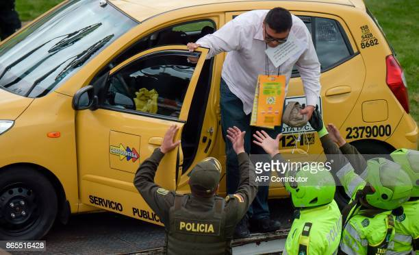 Police officers try to disperse a protest staged by taxi drivers against the private hire company Uber in Bogota on Ocotober 23 2017 / AFP PHOTO /...