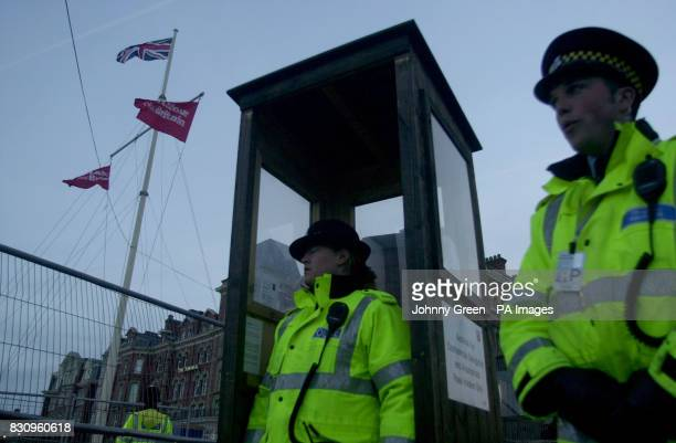 Police officers try to keep warm during the last hour of their shift after keeping guard throughout the night outside the Imperial Hotel on Blackpool...