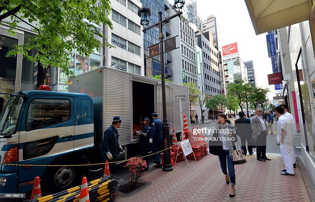 Police officers unload traffic cones to prepare for traffic control near sushi restaurant 'Sukiyabashi Jiro' in Tokyo on April 23, 2014. US President Barack Obama will reportedly dine at a tiny Tokyo sushi restaurant, a place with three coveted Michelin stars but only a handful of seats, ruled with an iron rod by its redoubtable 88-year-old owner, Jiro. Obama will come to Tokyo for a three-day visit from April 23 for and will have dinner with Japanese Prime Minister Shinzo Abe. AFP PHOTO / Yoshikazu TSUNO