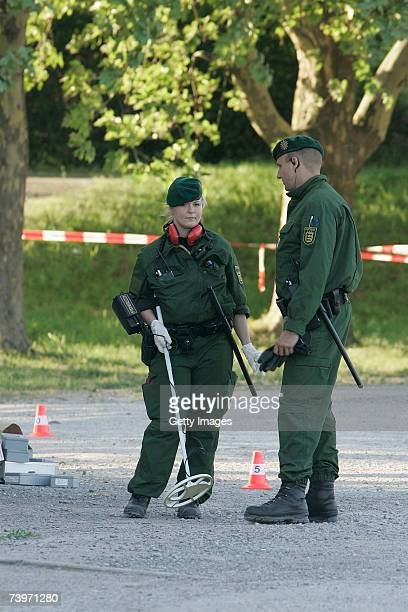 Police officers use metal detectors as they search following the shooting of two police officers at the Theresienwiese on April 25 2007 in Heilbronn...