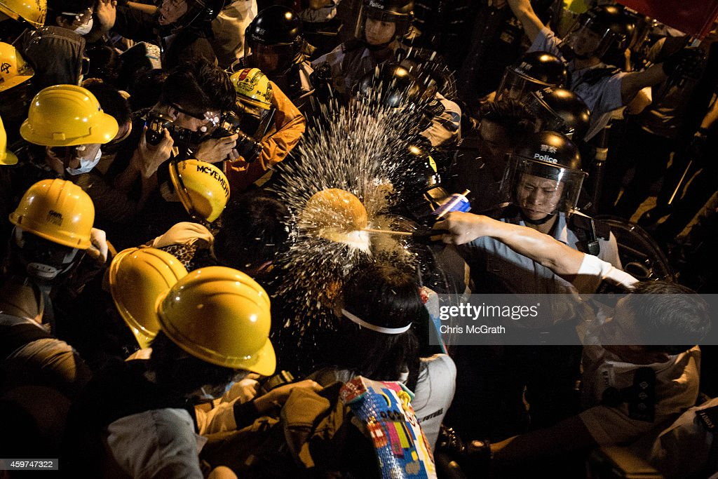 Police officers use pepper spray as they clash with prodemocracy protesters outside Hong Kong's Government complex on November 30 2014 in Hong Kong...