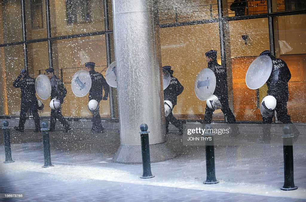 Police officers use shields to protect themselves from milk being thrown at them by dairy farmers staging a protest against European Union agricultural policies at the Place du Luxembourg, near the European Parliament, in Brussels, on November 26, 2012. Farmers demonstrated at the European Parliament in Brussels today with tractors and fake cows calling on political leaders to act on falling milk prices caused by overproduction in Europe.