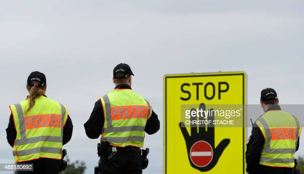 Police officers wait for passport control at a highway slip road at the GermanAustrian border near the village of Passau southern Germany on...