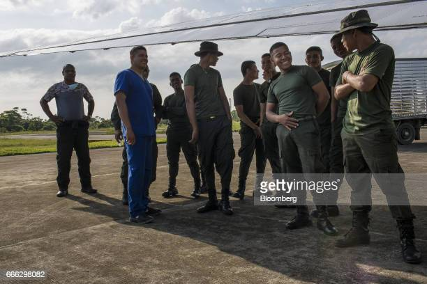 Police officers wait for the arrival of a cargo plane carrying disaster relief supplies at the Villagarzon Airport in Villagarzon Putumayo Colombia...