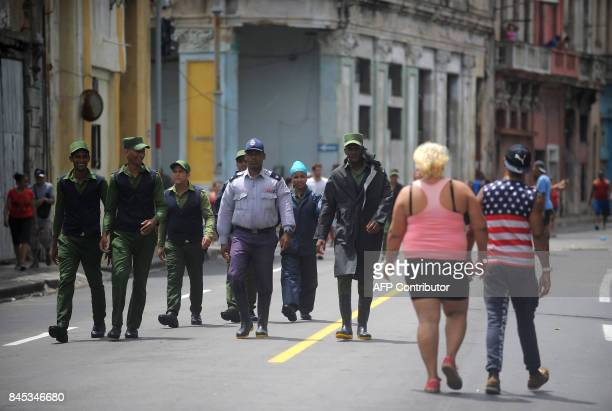 Police officers walk along a street of Havana on September 10 2017 Deadly Hurricane Irma battered central Cuba on Saturday knocking down power lines...