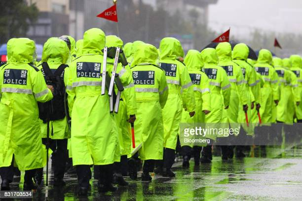 Police officers walk along the road during a rally against the deployment of the Terminal HighAltitude Area Defense system in Seoul South Korea on...