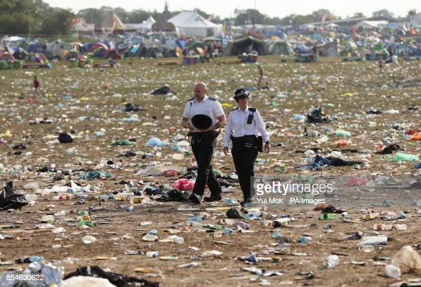 Police officers walk amongst the litter strewn around the Pyramid Stage area as the clean up operation begins at the Glastonbury Festival at Worthy...
