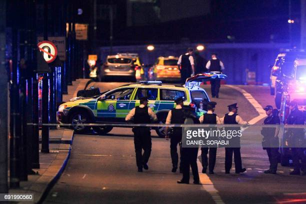 TOPSHOT Police officers walk at the scene of an apparent terror attack on London Bridge in central London on June 3 2017 Armed police fired shots...