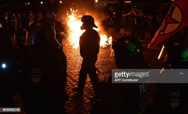 TOPSHOT Police officers walk in front of a fire started by protesters the 'Welcome to Hell' rally against the G20 summit in Hamburg northern Germany...