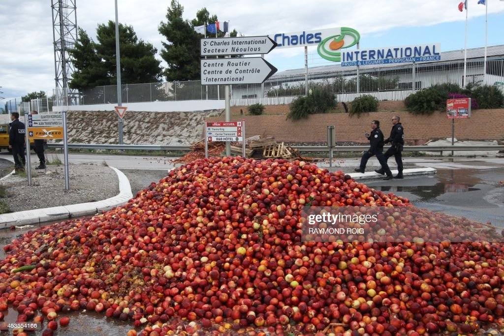 Police officers walk next to piles of nectarines and pallets dumped by farmers to block access to the Saint-Charles International market, one of Europe's main fruit and vegetable dispatch centres, on August 13, 2014 in Perpignan, southern France, to protest an 'economic dumping' allegedly practiced in Spain. Some 200 farmers blocked the Boulou border crossing Spain and France on August 13, 2014, before heading to the Saint-Charles International market and dumping piles of nectarines to block its access.