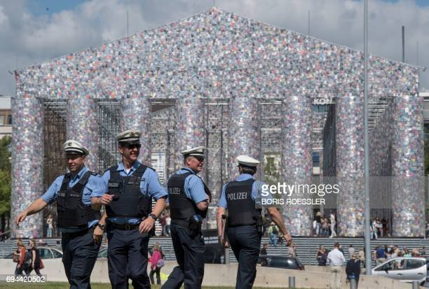 Police officers walk pass the 'Parthenon of Books' created by the Argentinian artist Marta Minujin during the official opening of the documenta 14 in...