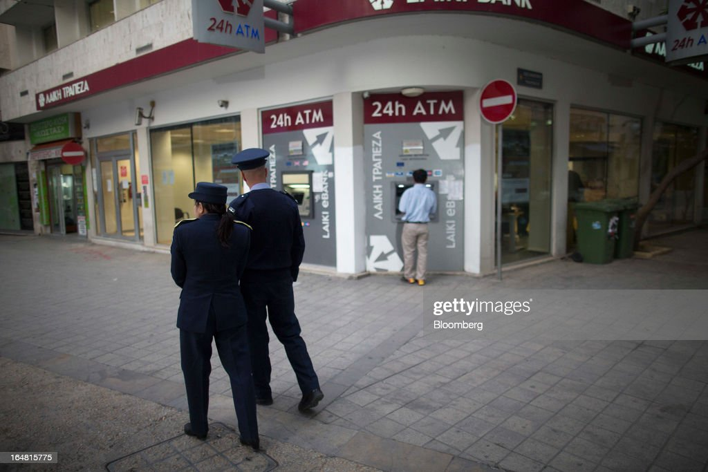 Police officers walk past a branch of Cyprus Popular Bank Pcl, also known as Laiki Bank, as banks open for the first time in two weeks in Nicosia, Cyprus, on Thursday, March 28, 2013. The Central Bank of Cyprus's capital controls will include a 300-euro ($383) daily limit on withdrawals and restrictions on transfers to accounts outside the country. Photographer: Simon Dawson/Bloomberg via Getty Images