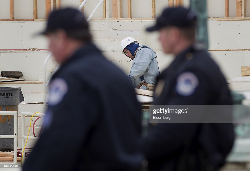 Police officers walk past a carpenter as he works on the construction of the platform being built on the west front of the U.S. Capitol in preparation for the inauguration ceremony of U.S. President Barack Obama in Washington, D.C., U.S., on Tuesday, Dec. 11, 2012. The presidential inauguration ceremony will take place on Jan. 21, 2013. Photographer: Andrew Harrer/Bloomberg via Getty Images
