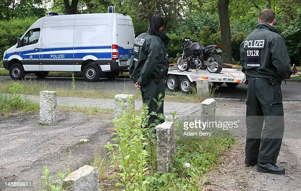 Police officers watch as a police van carries away a motorcycle that has been seized at the clubhouse of the motorcycle gang Bandidos Del Este on...