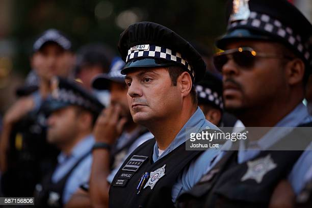Police officers watch as demonstrators protest the fatal police shooting of Paul O'Neal August 7 2016 in Chicago Illinois O'Neal an unarmed 18yearold...