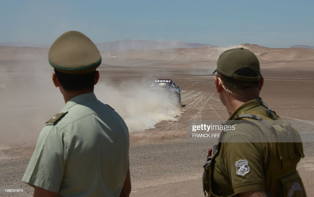 Police officers watch as Qatar's Nasser Al-Attiyah competes in the Stage 6 of the 2013 Dakar Rally between Arica and Calama, Chile, on January 10, 2013. The rally is taking place in Peru, Argentina and Chile from January 5 to 20.