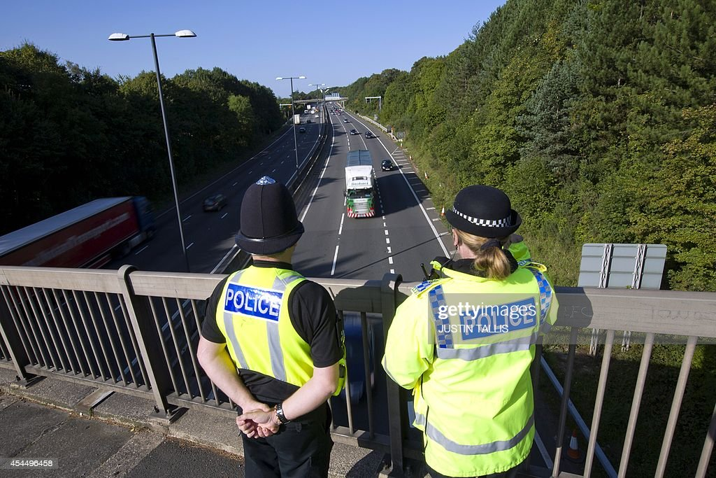 Police officers watch over the M4 motorway near to The Celtic Manor Resort the venue hosting the upcoming NATO summit in Newport south Wales on...