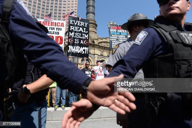 TOPSHOT Police officers watch protesters on the second day of the Republican National Convention on July 19 2016 in Cleveland Ohio About 50000 people...