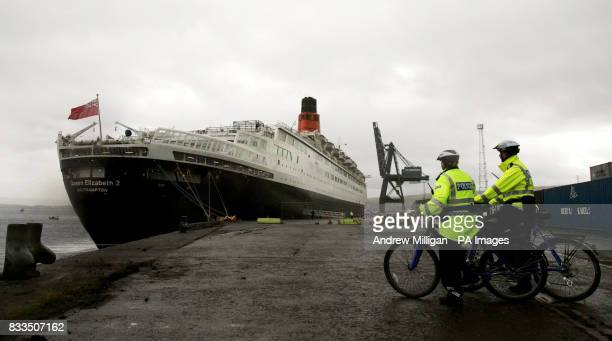 Police officers watch the QE2 after it arrived at the Ocean Terminal on the Firth of Clyde early this morning