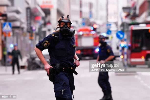 TOPSHOT Police officers wearing gas masks work at the scene where a truck crashed into the Ahlens department store at Drottninggatan in central...