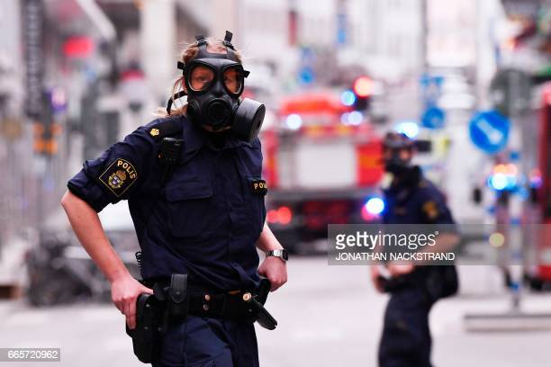 Police officers wearing gas masks work at the scene where a truck crashed into the Ahlens department store at Drottninggatan in central Stockholm...