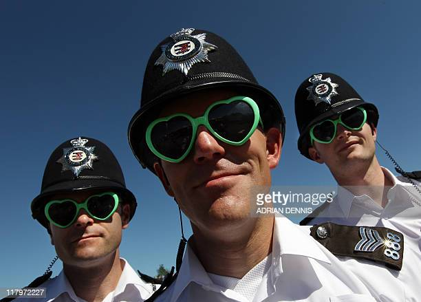 Police officers wearing identical sunglasses pose for a photograph during the last day of the Glastonbury festival near Glastonbury Somerset on June...