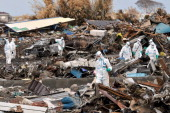 Police officers wearing radiation protective clothing continue search for bodies of the earthquake and tsunami vicitms amongst rubble 7km from the...