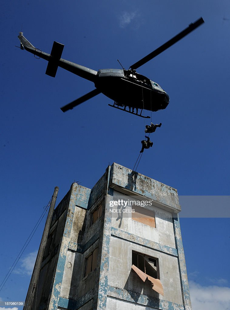 Police officers who were part of the Special Action Force (SAF) rapel from a helicopter during the Philippine National Police capability demonstration at the Camp Bagong Diwa in Manila on November 28, 2012. The drill is part of the security plan in anticipation of a possible rise in crimes during the coming Christmas season. The Philippines has the longest Christmas season in the world, which officially begins with nine pre-dawn masses nine days before December 25 and typically extends to the first week of January. AFP PHOTO/NOEL CELIS