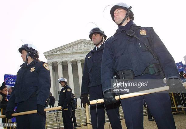 Police officers with riot gears stand guard during a protest December 11 2000 outside the US Supreme Court in Washington The US Supreme Court began...