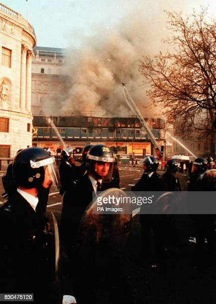 Police officers with riot shields and helmets stand in Trafalgar Square London after a protest against the Poll Tax erupted into a riot Firemen...