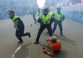 Police officers with their guns drawn hear the second explosion down the street The first explosion knocked down 78yearold US marathon runner Bill...