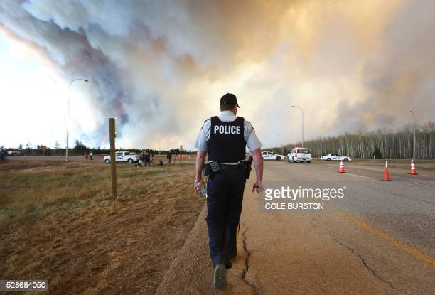 Police officers work around a road block as smoke rises from a forest fire along the highway near Fort McMurray Alberta on May 6 2016 Canadian police...