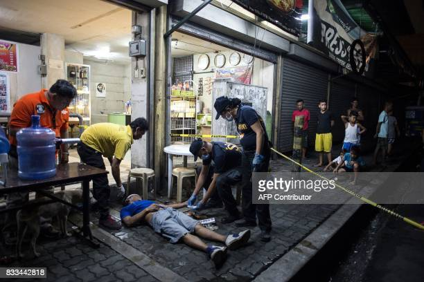 TOPSHOT Police officers work at a crime scene where an alleged drug dealer was killed during a police antidrug operation in Manila on August 17 2017...