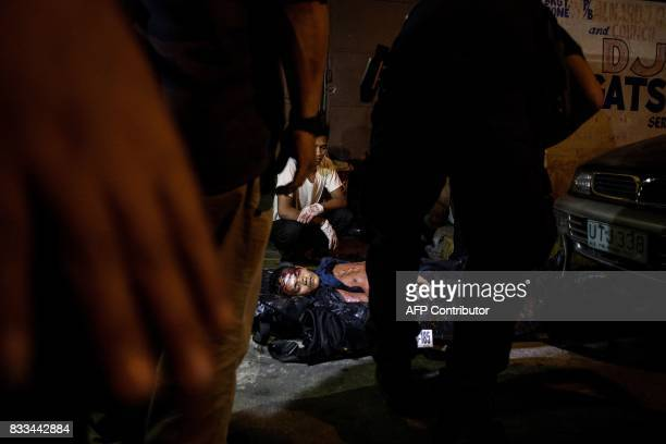 Police officers work at a crime scene where an alleged drug dealer was killed during a police antidrug operation in Manila on August 17 2017 Police...