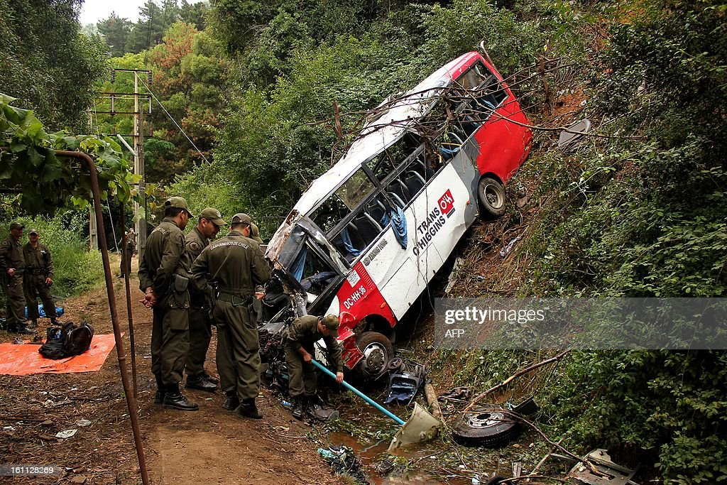 Police officers work at the site of a bus accident in Tome, in Biobio province, some 500 km south of Santiago, on February 9,2013. At least 15 people were killed and 19 others were injured when the bus full of passengers fell into a ravine in central Chile, a local official said.